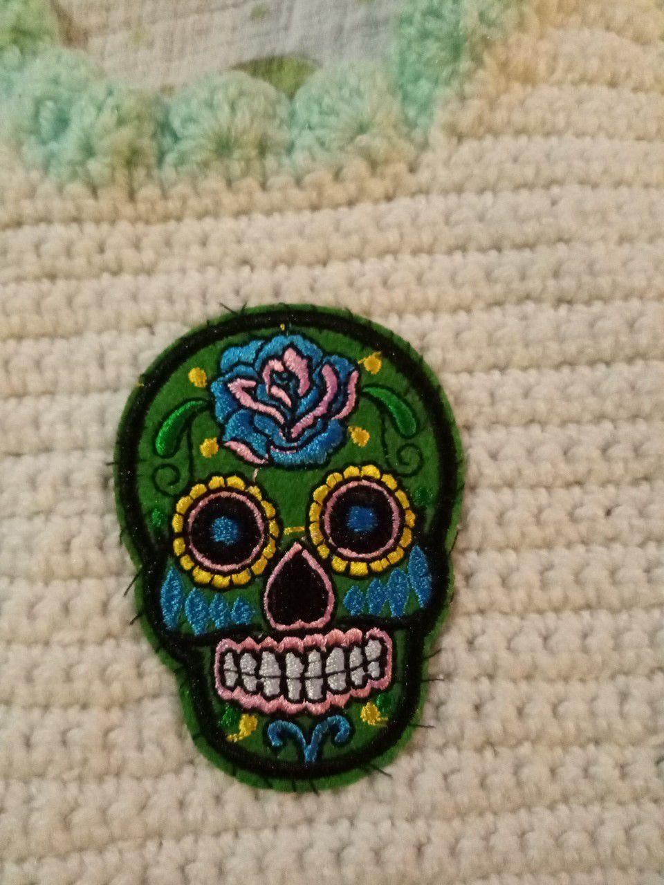 Hand-knitted sugar skull baby bib