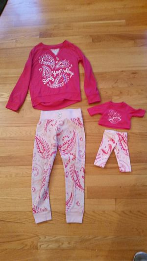 Photo American girl brand doll and child matching pajamas