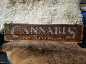 Photo Cannabis Sativa Vintage painted sign. Beautiful piece of artwork. 32 in length. 7 1/2 in tall/wide. Great artistry in the sign. $85. (Sign only.)