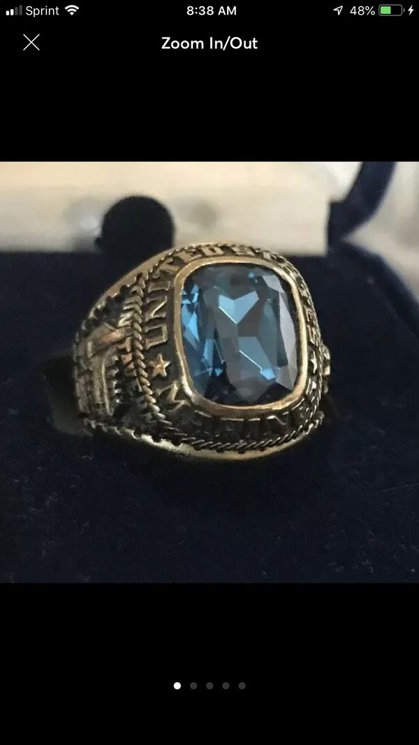 Very nice United States Marine Corp men's ring made by Jostens  This one is  a size 7, made of yellow Lustrium with a faceted blue stone  Has the Jost