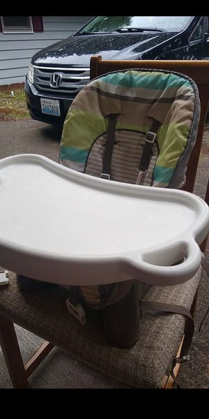 Photo Fisher Price high chair booster seat. This booster seat straps to a kitchen chair.