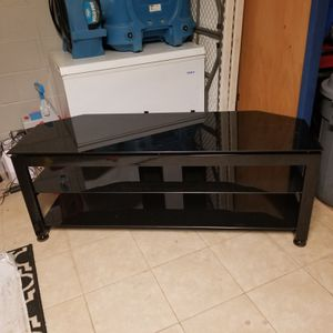 Photo Heavy duty 3 tiered black glass TV stand. Like new hardly used. Decide to mount tv to the wall instead. My loss can be your gain.