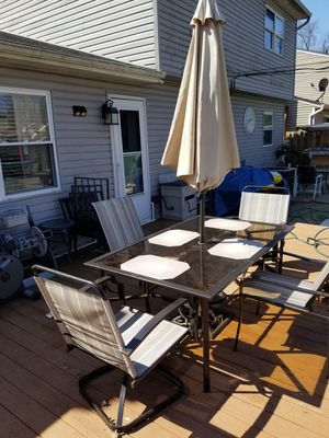 Photo Patio set glass top table with four chairs and umbrella