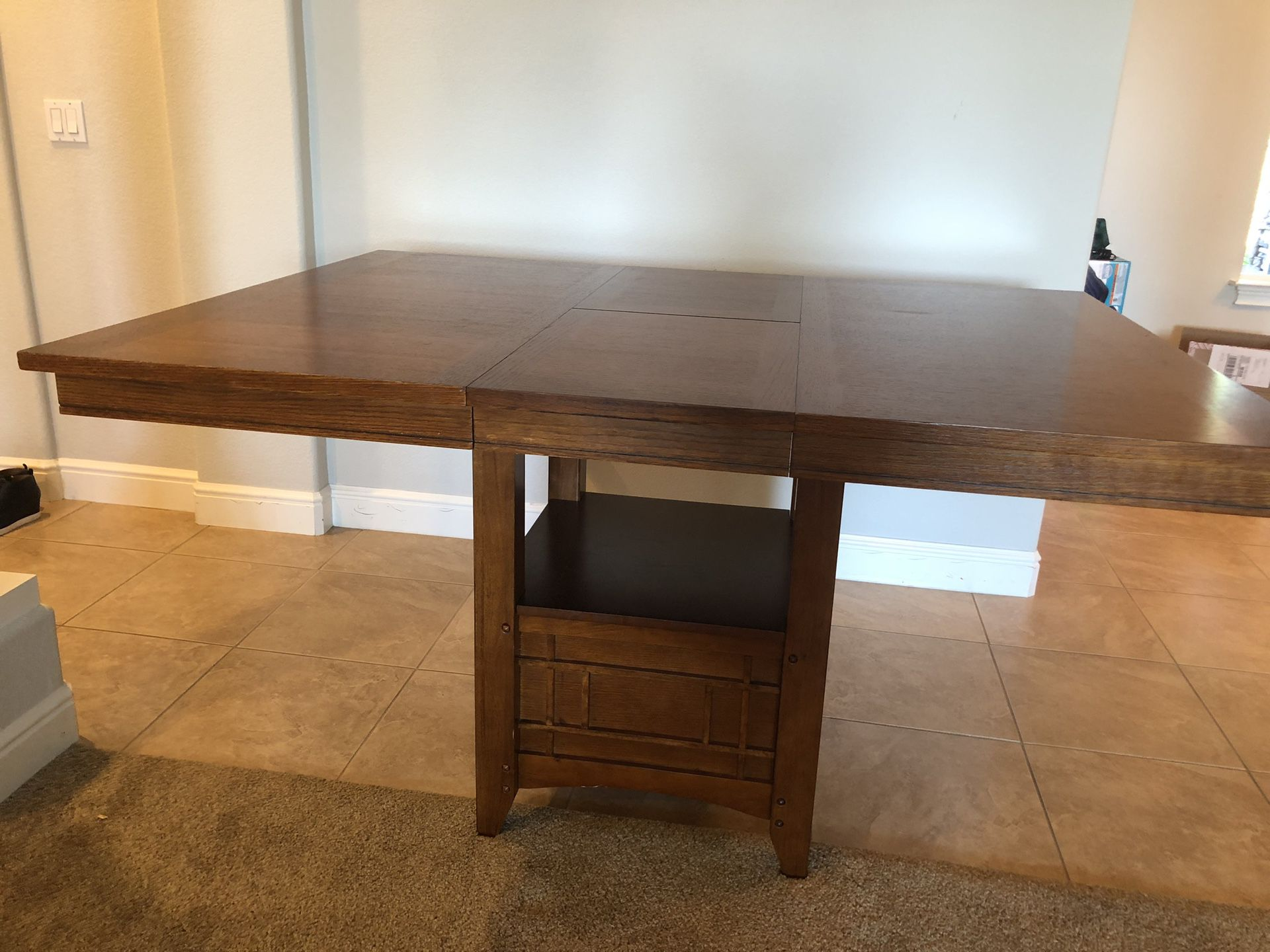 """Bar height wood dining table. Can be square 48""""x48"""" or rectangle with a middle leaflet. It has a storage and shelf under and is used but as good as n"""