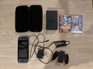 Photo Nintendo switch with all the cables and accessories, plus 2 games including smash