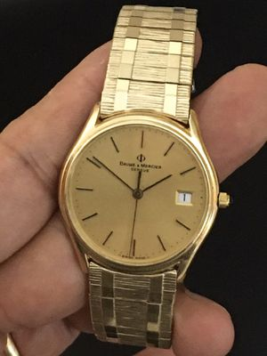 Photo Baume & Mercier solid 14k. Yellow gold. Woman's Swiss made quartz movement watch. New battery. Band is gold-filled. 35mm.