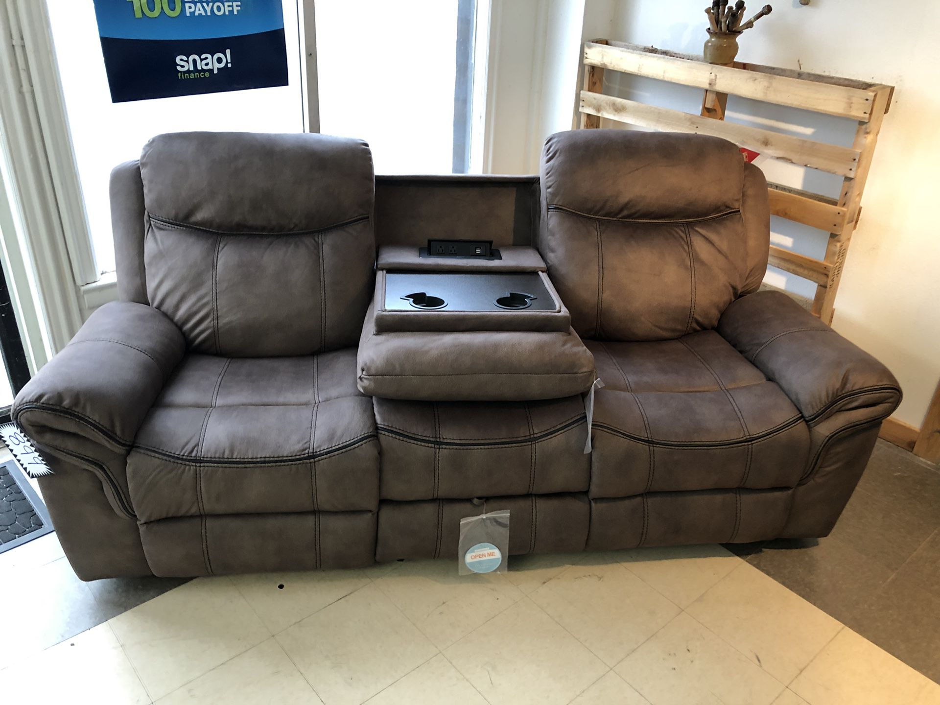WATER RESISTANT Microfiber smooth bomber jacket material recliner. Pull out table with cup holders. Built in USB ports and wall plug ins. Hidden draw