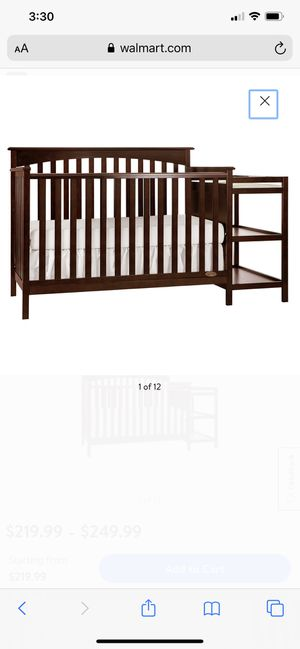 Photo Baby crib with attached shelves and changing station.