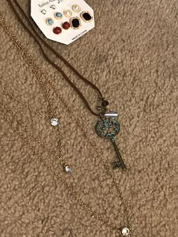 Three piece necklace that, earrings, key necklace and Larry necklace gold color six dollars for all Thumbnail