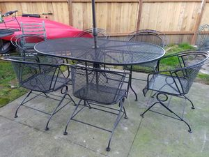 Photo Wrought iron dining patio set oval table with 6 rocking chairs and big umbrella