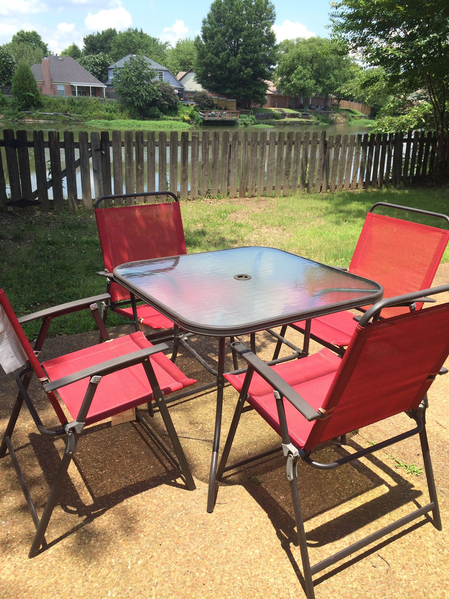 Glass outside table with 4 red chairs