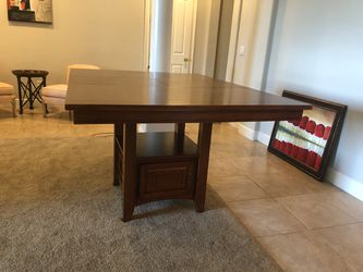 """Bar height wood dining table. Can be square 48""""x48"""" or rectangle with a middle leaflet. It has a storage and shelf under and is used but as good as n Thumbnail"""