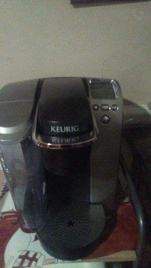 Photo Almost brand-new keurige machine. Only used one time and bought a new one come with 2 boxes of k cups 24 total. Cups ..Has a automatic set,alarm