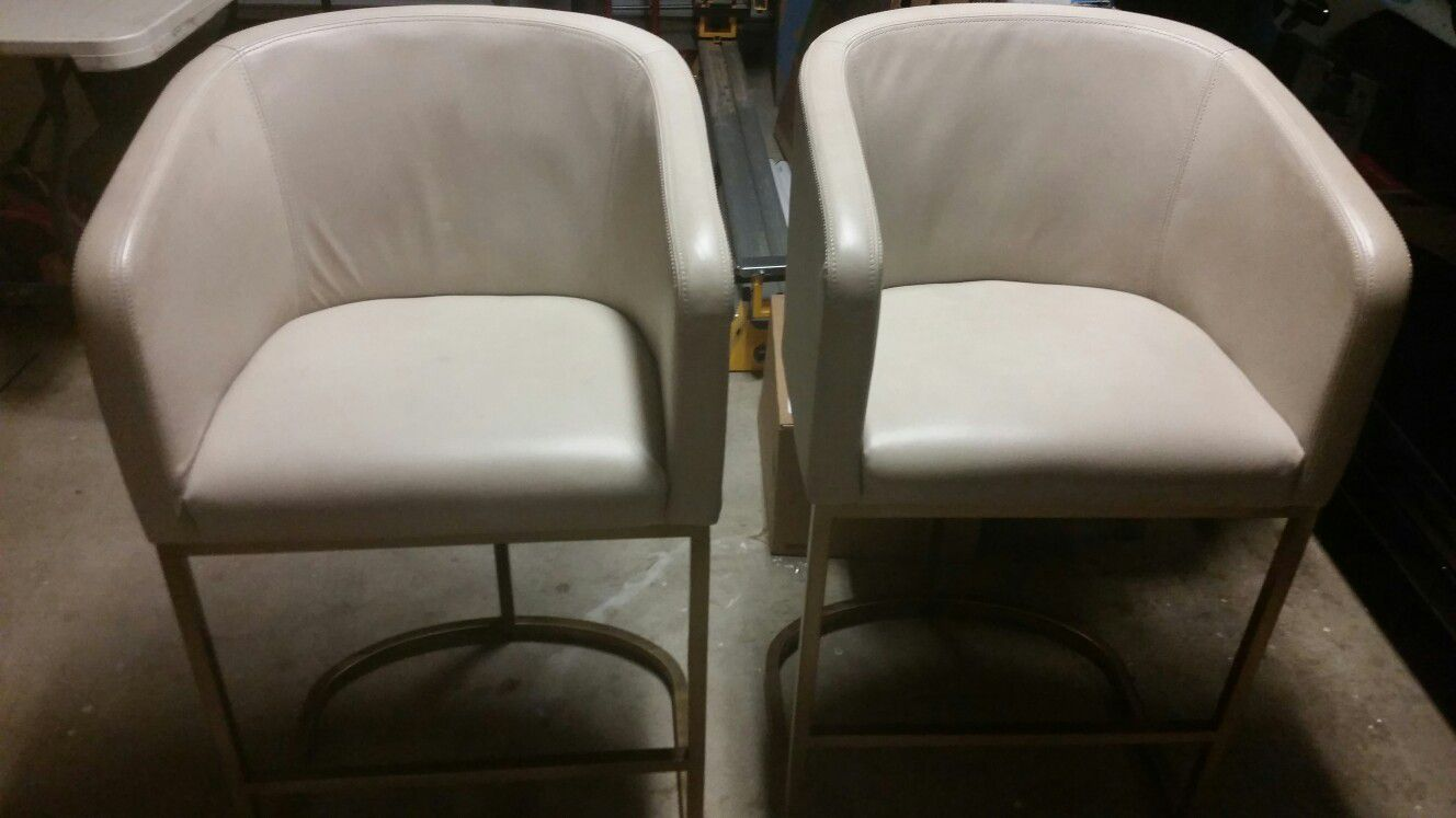 Two Restoration Hardware Modern leather and brass counter stools.
