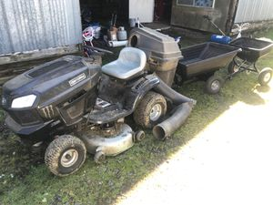 Photo Riding lawn mower with bagger and two trailers