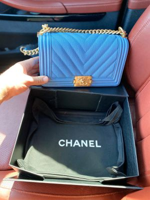 Photo AUTHENTIC Boy Chanel Handbag In Baby Blue with Caviar leather and champagne gold hardware.