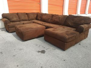 Photo Used brown ashley sectional sofa with ottoman